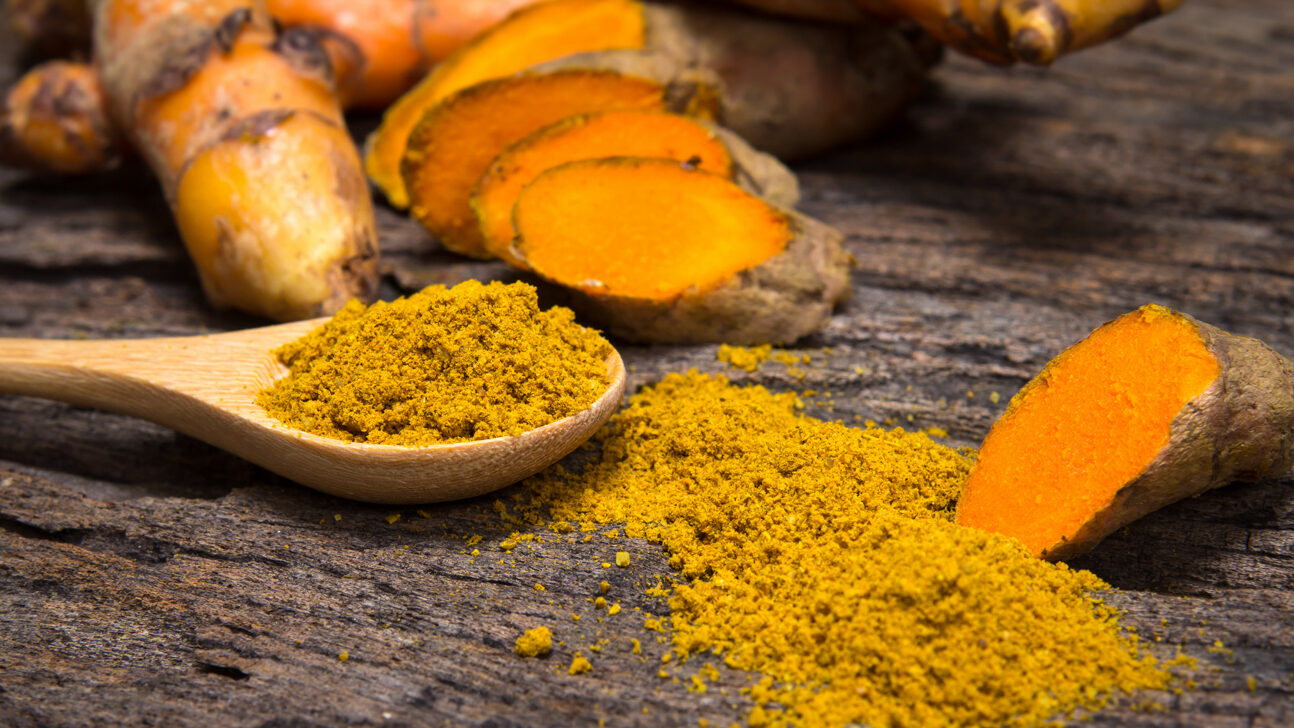 turmeric-powder-in-spoon-and-roots-on-wooden-plate