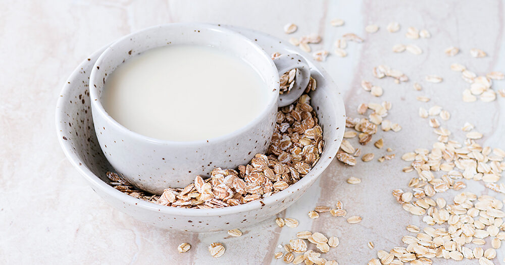 a-cup-of-oat-milk-in-bowl-of-oats-on-a-marble-surface